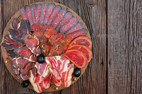 Close up of assorted sliced dry-cured meat on the wooden plate background - Stock Photo - Images