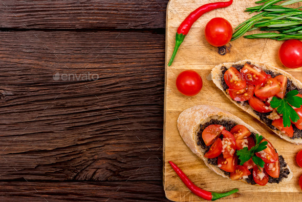 Fresh tasty bruschetta with truffle sauce, chili, parsley and tomates. Top view - Stock Photo - Images