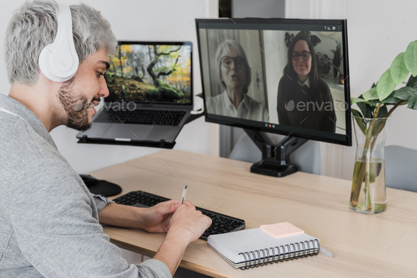 Young hipster man having video call with colleagues on computer app - Multi generational videocall - Stock Photo - Images