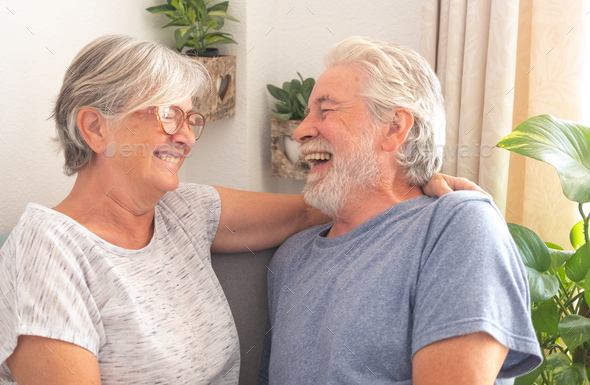 Cheerful senior couple sitting in living room at home,laughing carefree - Stock Photo - Images