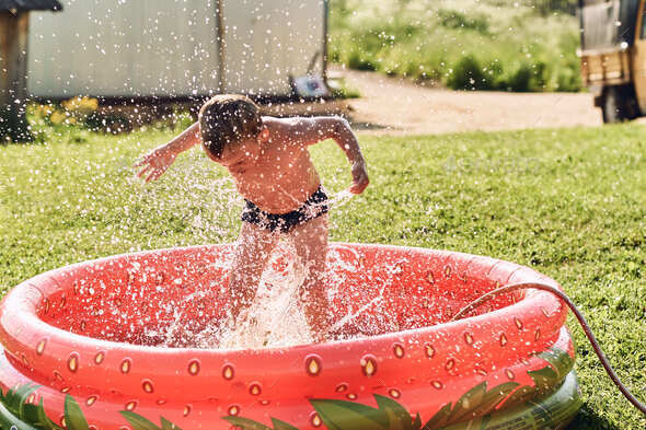 A boy frolics in a small red rubber pool in the summer. - Stock Photo - Images