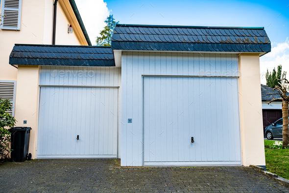 wide garage door and concrete driveway in front - Stock Photo - Images