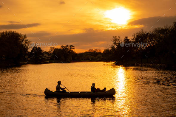 Silhouette of couple with dog kayaking in the lake at sunset - Stock Photo - Images