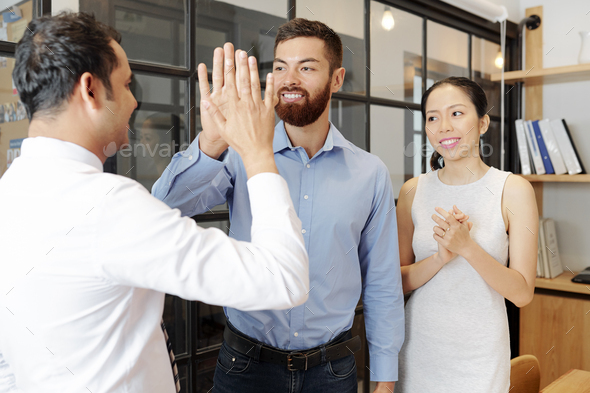 Colleagues giving each other high five - Stock Photo - Images