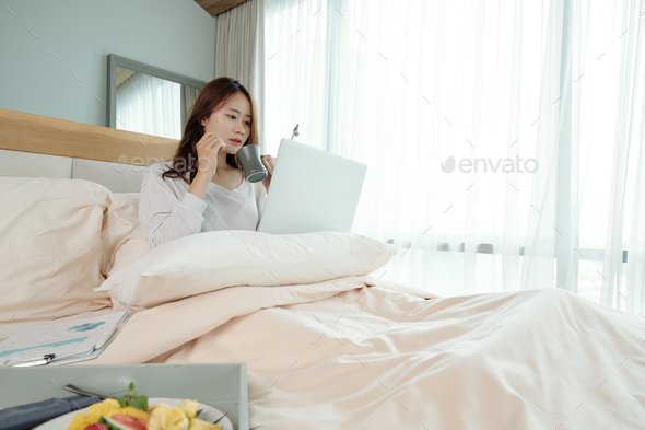 Student working on laptop in bed - Stock Photo - Images