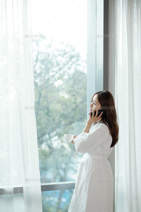 Woman in bathrobe calling on phone - Stock Photo - Images