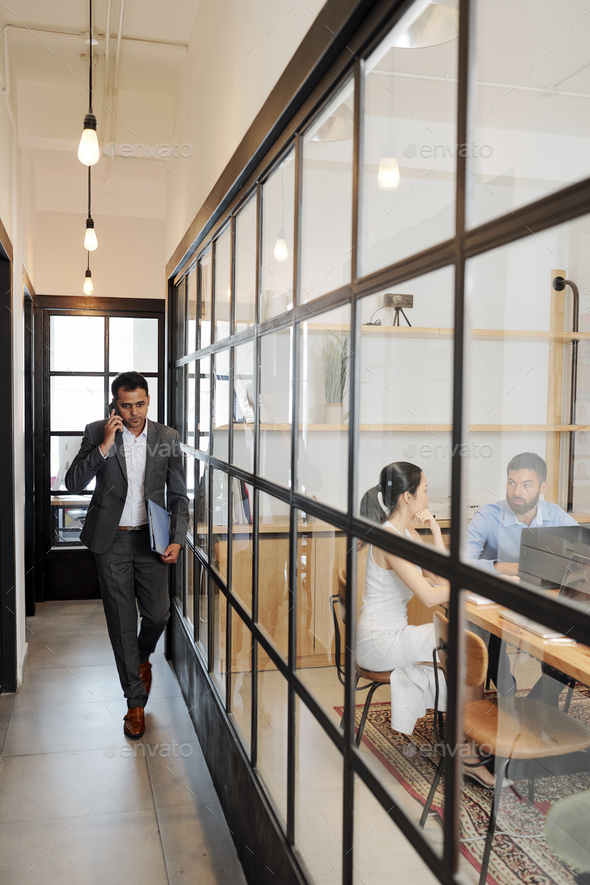 Entrepreneur walking along office corridor - Stock Photo - Images