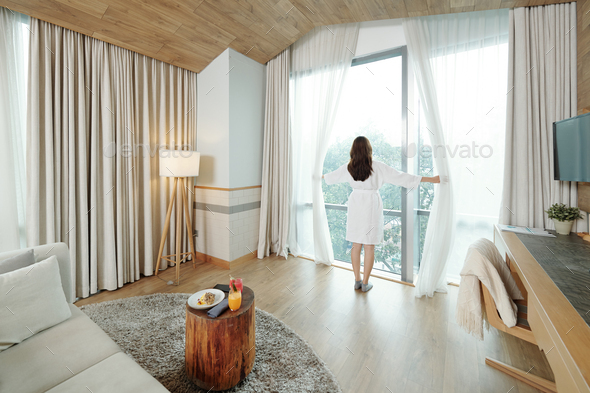 Woman opening curtains - Stock Photo - Images