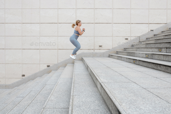 Sportswoman jumping up the stairs - Stock Photo - Images