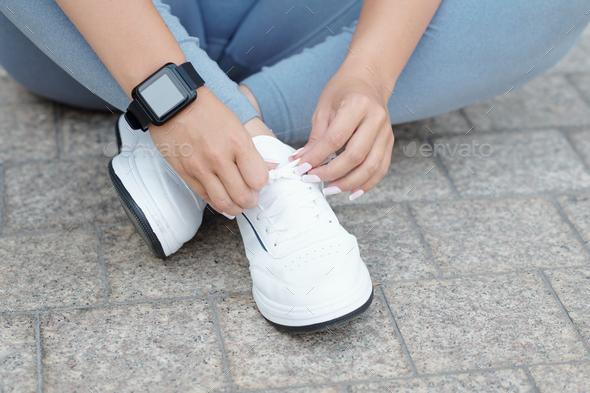 Sportswoman tying shoelaces - Stock Photo - Images