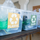 A group of plastic containers with donation clothes on a table - PhotoDune Item for Sale
