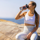 Female Athlete Drinking Water During Outdoor Workout by the Sea - PhotoDune Item for Sale