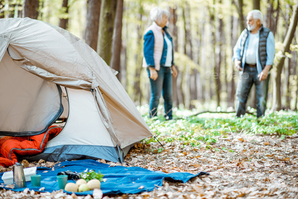 Campsite with senior couple in the forest - Stock Photo - Images