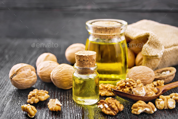Oil walnut in two jars on dark board - Stock Photo - Images