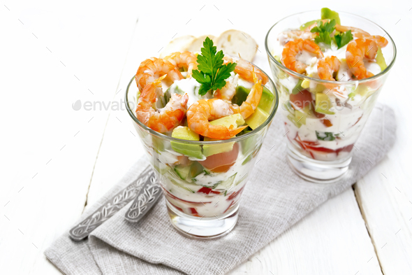 Salad with shrimp and avocado in two glasses on light board - Stock Photo - Images