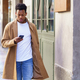 Young black man consulting his phone while walking down the street - PhotoDune Item for Sale