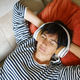 Middle-aged woman listening to soothing music with headphones lying on her sofa - PhotoDune Item for Sale
