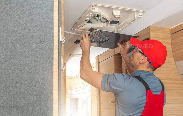 Men Repairing Air Condition Unit Inside Modern Travel Trailer - Stock Photo - Images