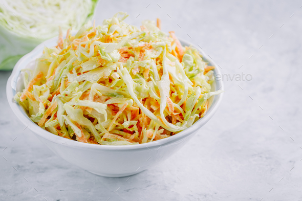 Traditional coleslaw salad with fresh sliced carrots and cabbage in a white bowl - Stock Photo - Images