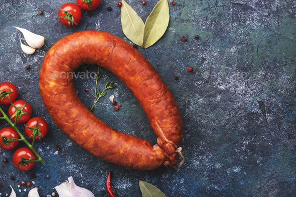 Smoked sausage circle on blue kitchen table - Stock Photo - Images