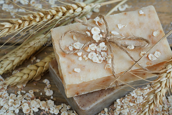 Natural handmade soap, oat flakes and wheat ears on wooden background - Stock Photo - Images