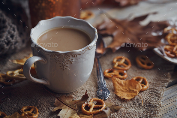 Autumn leaves, hot steaming cup of coffee and a warm scarf - Stock Photo - Images