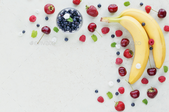 Raspberry, sweet cherry, banana and bilberry on white wooden background - Stock Photo - Images