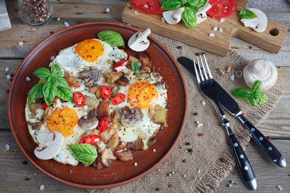 Fried eggs with mushrooms, tomatoes and basil on rustic wooden table - Stock Photo - Images