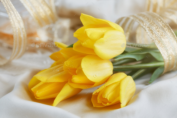 Yellow tulips, perfume and gold ribbon - Stock Photo - Images