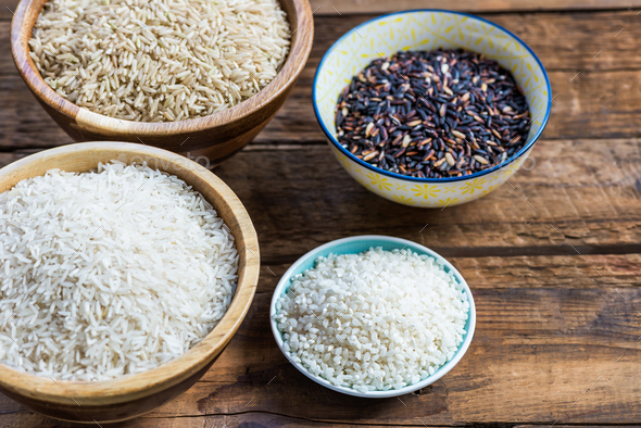 Different types of rice in wooden bowls such as basmati, brown a - Stock Photo - Images
