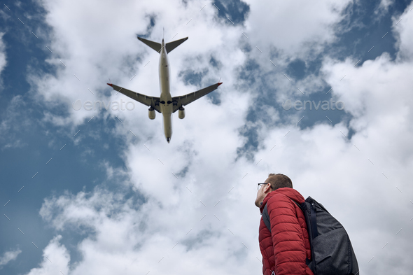 Man looking up at flying airplane against cloudy sky - Stock Photo - Images