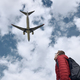 Man looking up at flying airplane against cloudy sky - PhotoDune Item for Sale