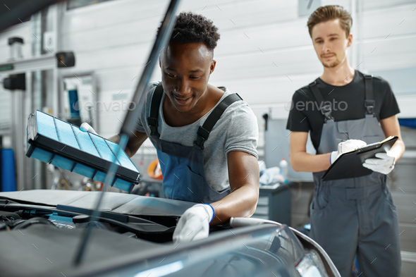 Two male workers repairs engine, car service - Stock Photo - Images