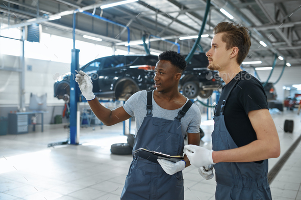 Two male mechanics talking in car service - Stock Photo - Images