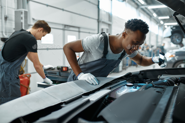 Two male mechanics inspects engine, car service - Stock Photo - Images