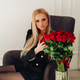Attractive blonde model in black touching red roses - PhotoDune Item for Sale