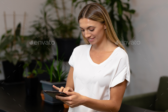 Portrait of caucasian businesswoman using digital tablet and smiling - Stock Photo - Images