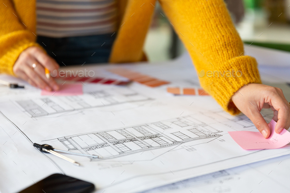 Midsection of caucasian businesswoman writing and placing memo notes on blueprint - Stock Photo - Images
