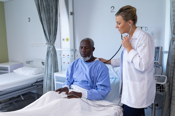 Caucasian female doctor examining with stethoscope african american male patient in hospital room - Stock Photo - Images