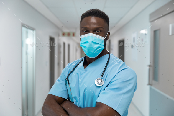 Portrait of african american male doctor wearing face mask standing in hospital corridor - Stock Photo - Images