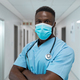 Portrait of african american male doctor wearing face mask standing in hospital corridor - PhotoDune Item for Sale