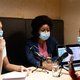 Diverse group of female business colleagues wearing masks in discussion speaking to microphones - PhotoDune Item for Sale