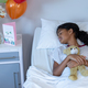 Sick mixed race girl holding teddy bear lying asleep in bed in a hospital ward - PhotoDune Item for Sale