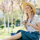 A confident woman sitting on the grass with a camera in a city park on a sunny spring morning. - PhotoDune Item for Sale