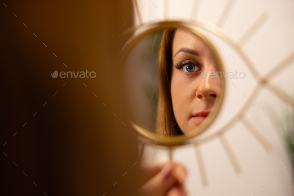 Young Woman Looking At Her Reflection In Beauty Clinic - Stock Photo - Images