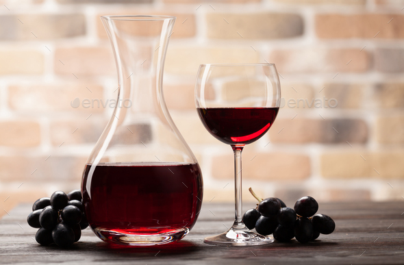 Wine decanter, glass of red wine and grapes - Stock Photo - Images