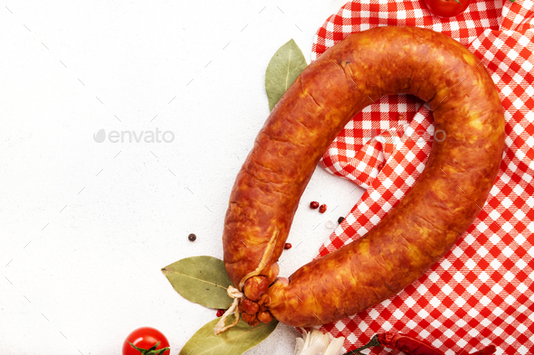 Smoked sausage circle on white kitchen table - Stock Photo - Images