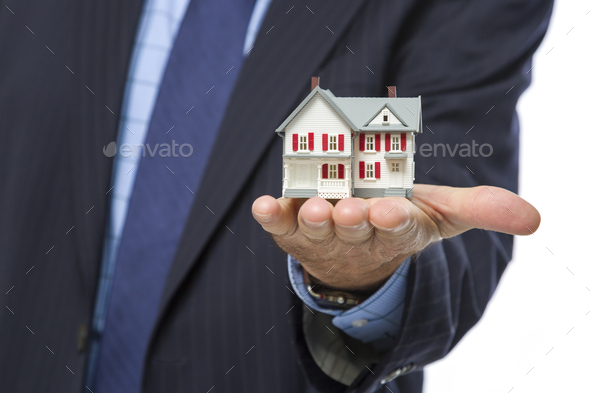 Male Real Estate Agent Holding Miniature House in Palm - Stock Photo - Images