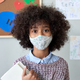 African school child girl wearing face mask in classroom, headshot portrait. - PhotoDune Item for Sale