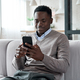 African american man using mobile apps sitting on couch at home. - PhotoDune Item for Sale